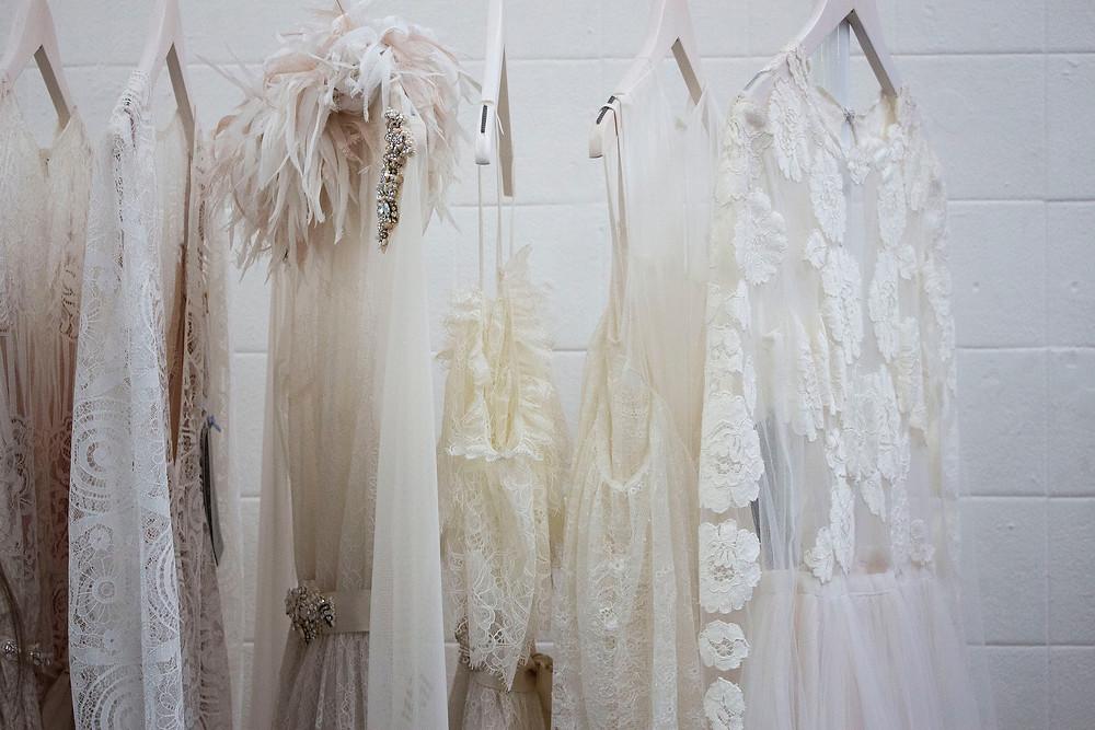 שמלות כלה תלויות על קולב