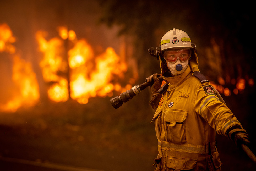 Milton Rural Fire Service volunteer Stacey Wilson holds the end of a containment line during a bushfire in the coastal town of Bawley Point on 5 December 2019.