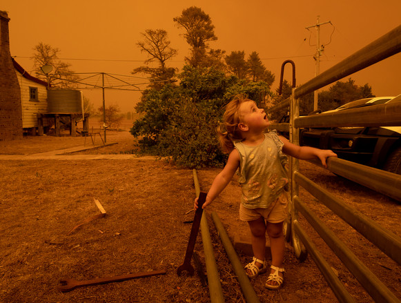 One-year-old Chelsea Povey watches the sky darken over the family property as the Clear Ridge bushfire advances towards the town of Colinton on 1 February 2020.