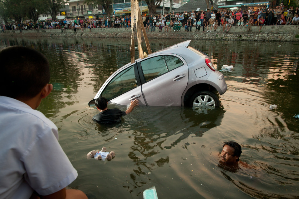 Spectators watch a vehicle being salvaged after a driver accidentally ended up in Chiang Mai's old moat on 23 February 2012.