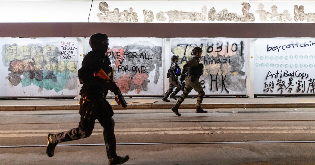 Police run past a tram stop marked with graffiti supporting the protest movement as they chase anti-government protesters in Hong Kong's Central district on the evening of 1 January 2020.