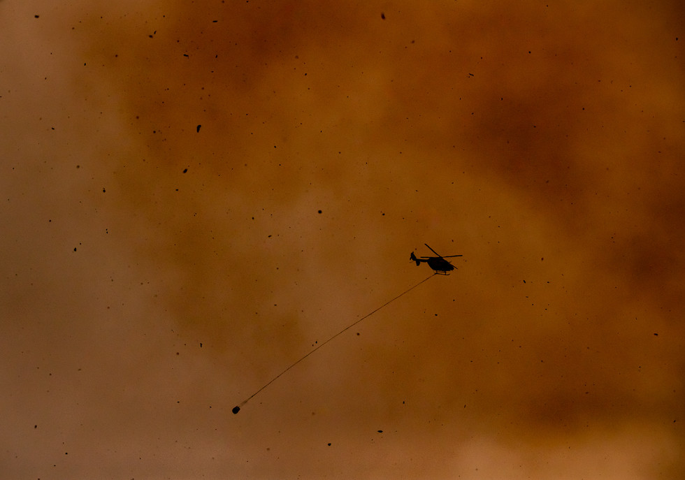 Ash falls from the sky as firefighting helicopters attack a bushfire in the coastal town of Bawley Point on 5 December 2019.
