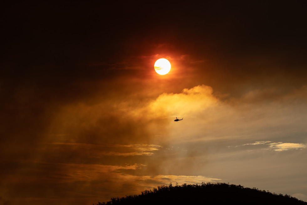 A firefighting helicopter flies towards the Orroral Valley bushfire which broke out in the Namadgi National Park on 27 January 2020.