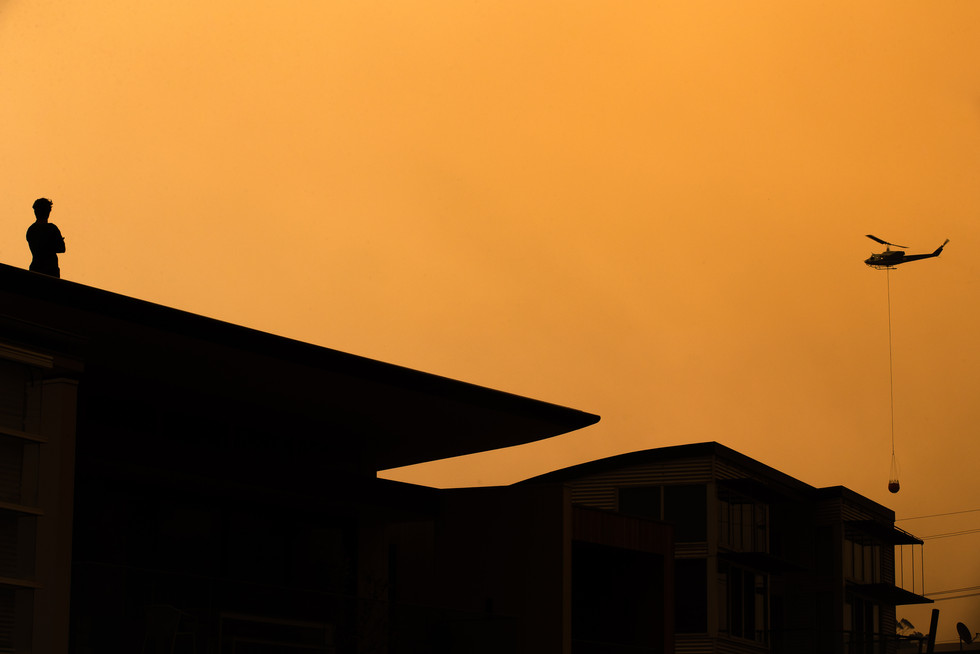 A Bawley Point resident watches from his rooftop as firefighting aircraft battle a bushfire in the coastal town on 5 December 2019.