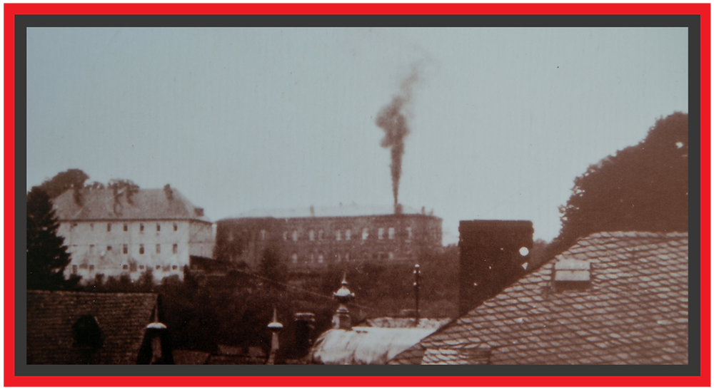 A white hospital on the left with a black building attached to it on the right. On the roof of the black building is a large chimney with ashes coming out the top.
