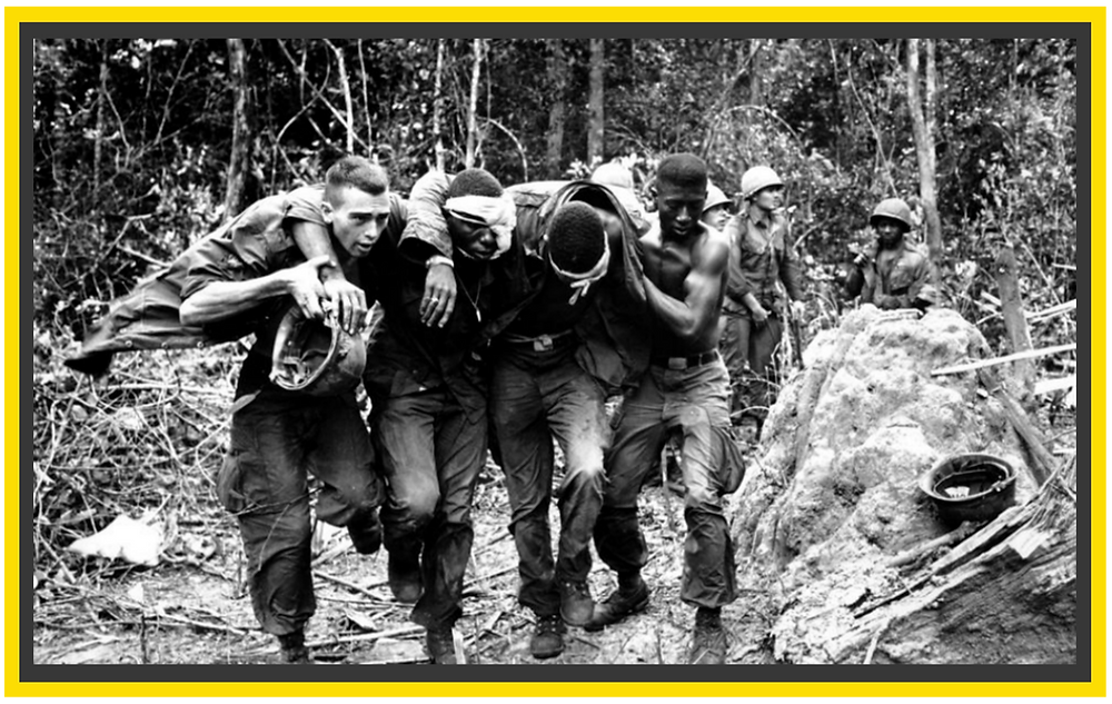 4 soldiers in Vietnam (1 white, 2 black) with arms linked over each other's shoulders, a few of them are injured.