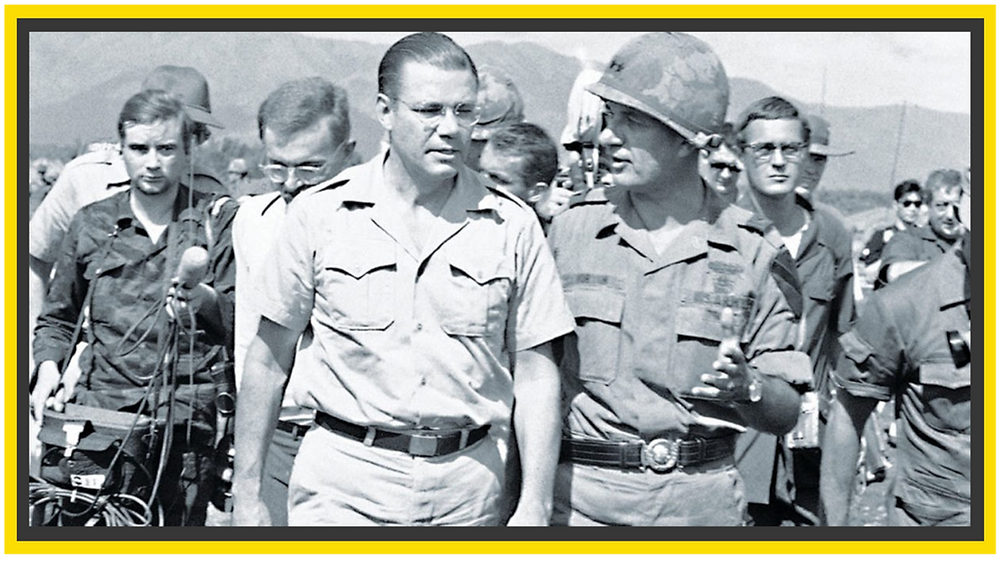 Robert McNamara, who is a white man wearing glasses and a white shirt and pants walking with soldiers wearing hard hats and camouflage uniforms. One man is holding a mic to him from behind.