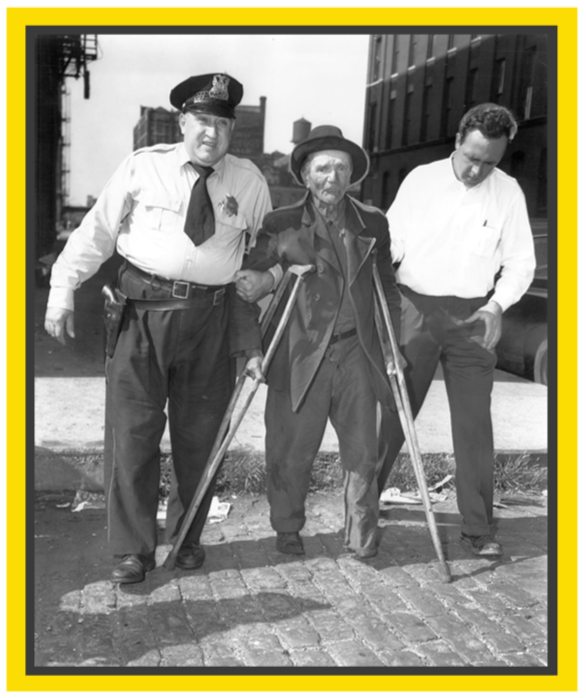 Black and white photo of 2 policemen with arms through the arms of an elderly man with crutches.