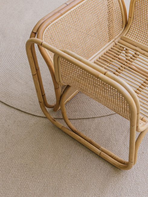 Wabi sabi minimalist interior with large natural round jute rug and design chair