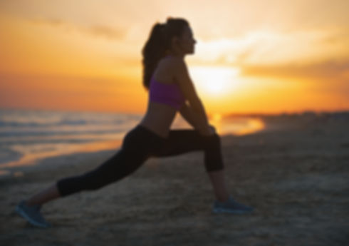 healthy looking woman working out in the early morning hours on a beach