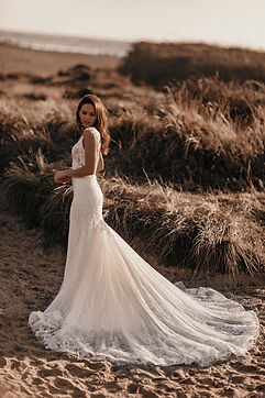fit and flare wedding dress with lace trim and lace appliques on beach