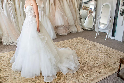 woman wearing white princess style wedding dress in bridal boutique