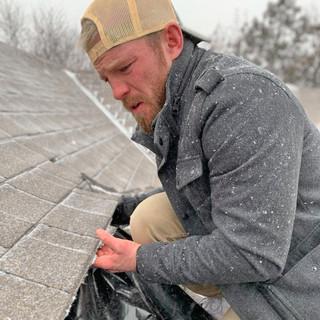 Paul Sanders of Murray Roofing Repairing Shingles in a Snow Storm