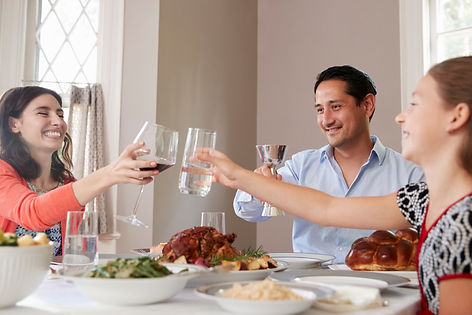 Jewish family raising glasses at their catered dinner