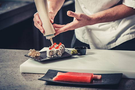 Sushi chef, adding the final touches to their presentation of a roll