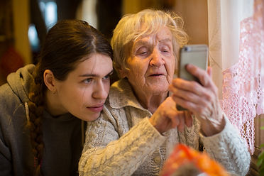 Elderly woman looks at a smartphone, wit