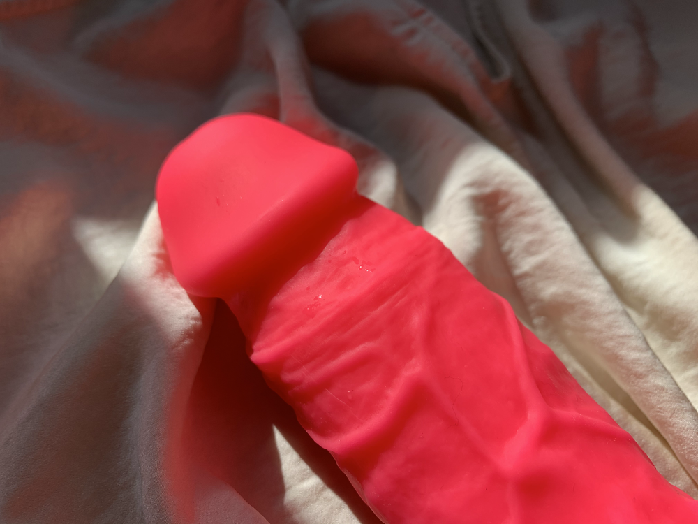 neon pink dildo up close showing jutting out coronal ridge