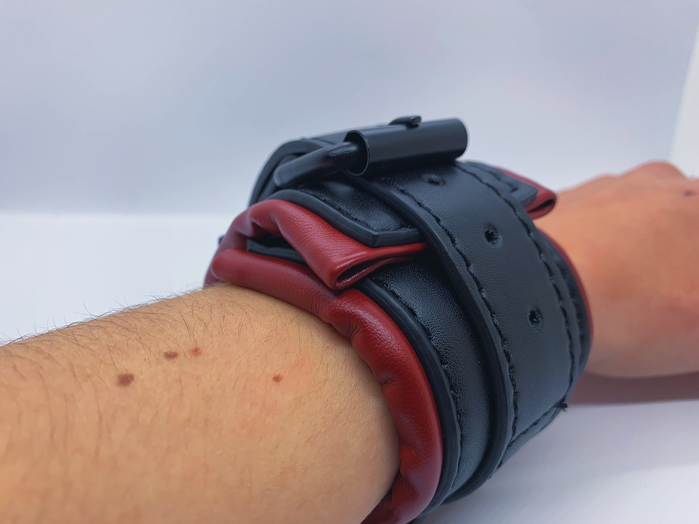 arm on white surface with red and black vegan leather handcuff with slightly overlapping material