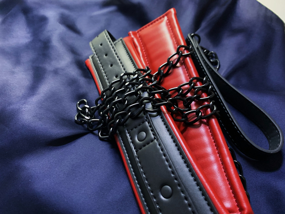 red and black vegan leather collar with metal chain leash on navy satin fabric