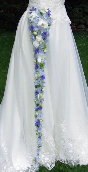 Feminine, trailing bridal bouquet with white orchids and blue delphinium and hydrangea