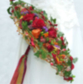 Contemporary gold and red bridal bouquet with ribbons