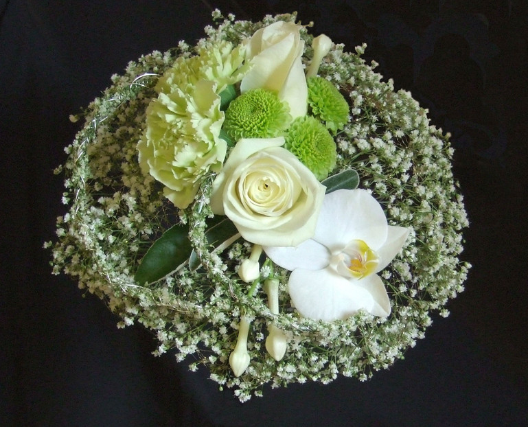 Delicate round gypsophila bouquet with orchids and roses