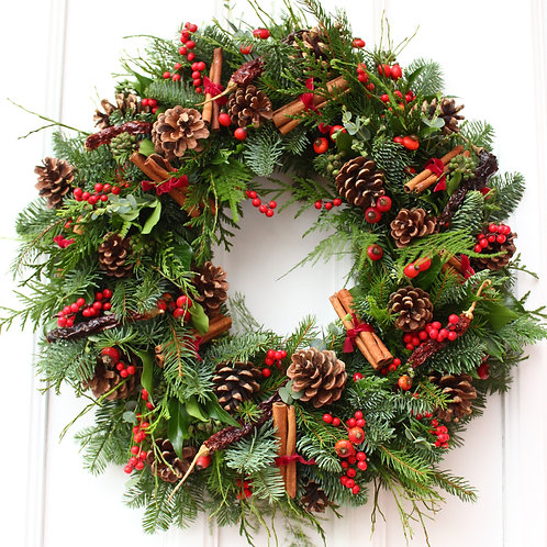 christmas wreath with red berries and pine cones