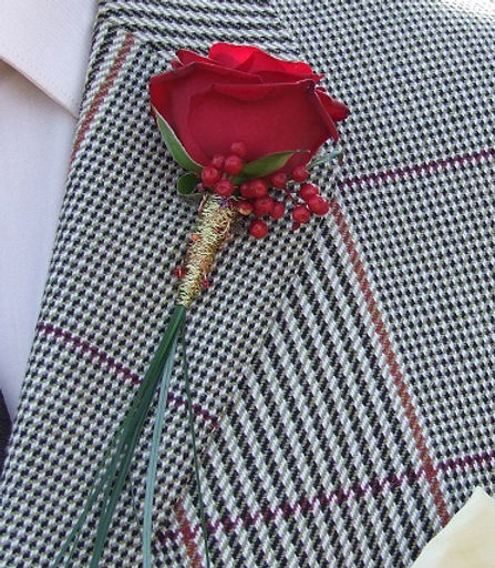 Red rose boutonniere with pepper berries