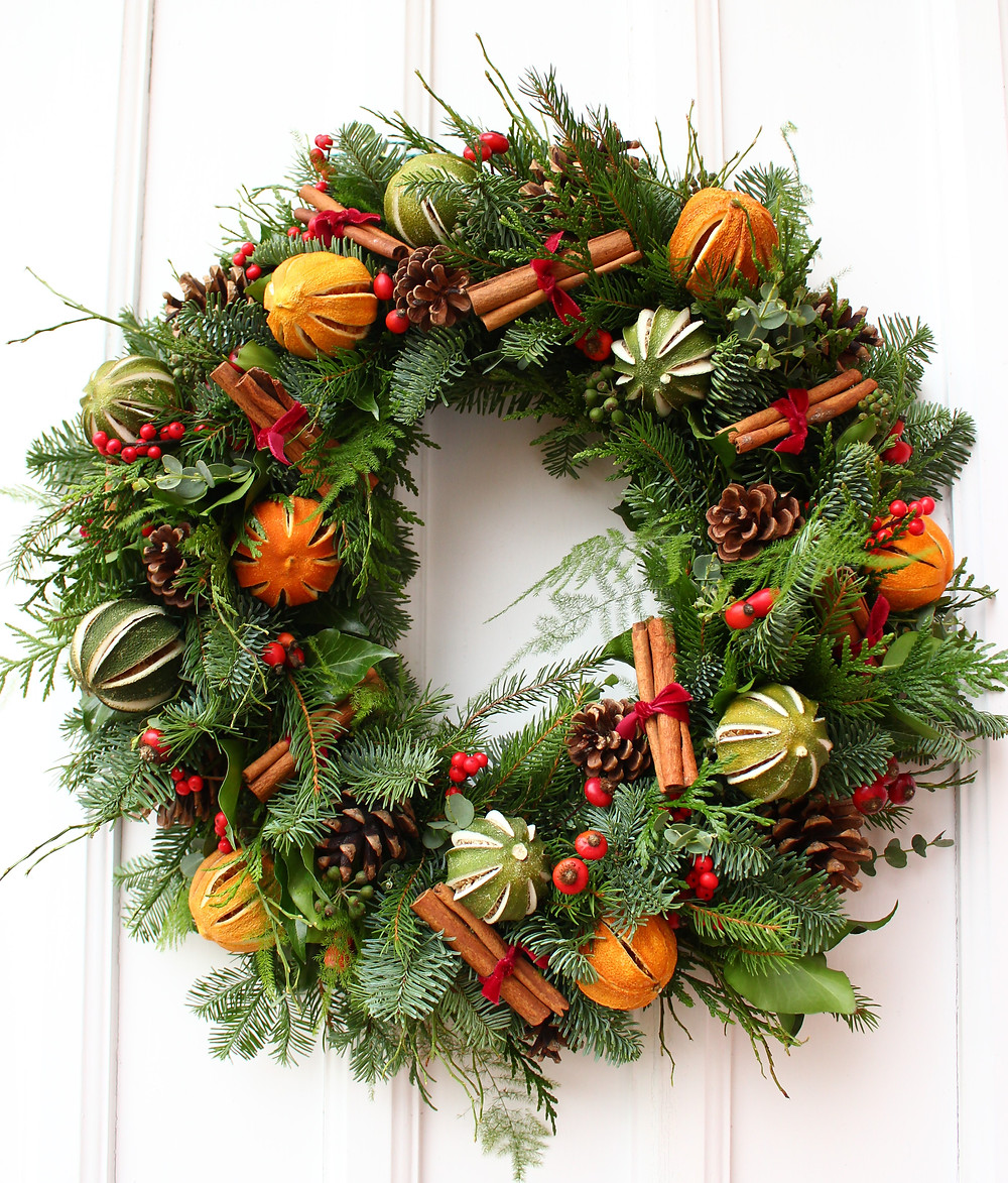 Christmas wreath with cones, cinnamon, dried oranges and limes