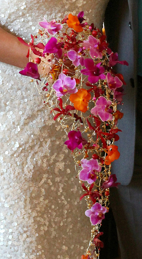 Delicate cerise orchid bouquet on a gold wire base