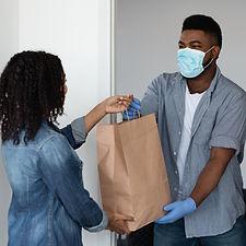 Food delivery during coronavirus. Black courier guy wearing medical mask delivering grocer