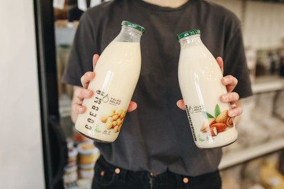 person-holding-bottles-with-milk-3735192