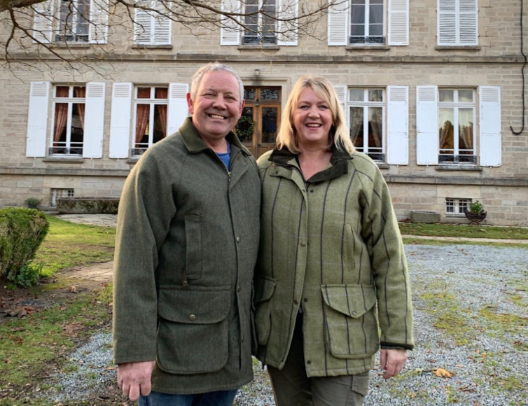 two people stood in front of a large french house