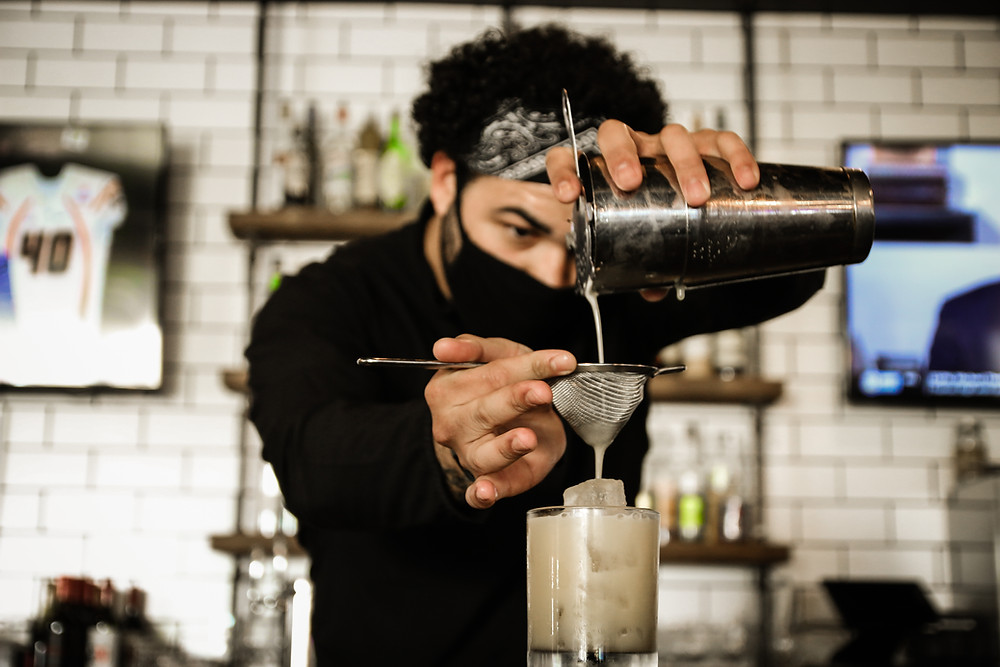 Bartender pours drinks with mask on to follow CDC guidelines