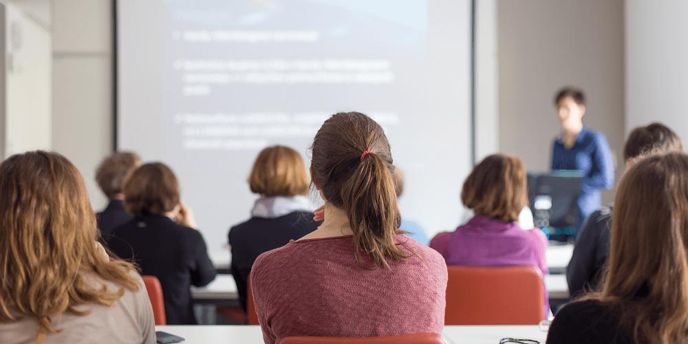 Hintere Ansicht von Teilnehmern, die Vorträge hören und Notizen machen. Wissenschaftliche Konferenz.
