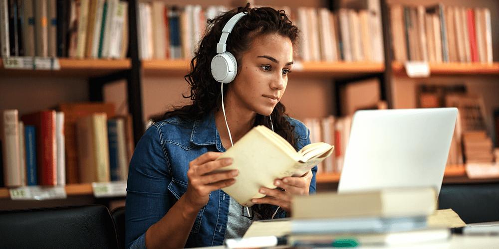 Die Studentin studiert in der Bibliothek. Sie lernt online und nutzt Laptop