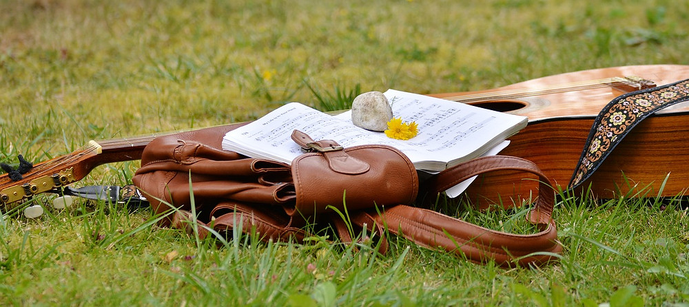 Acoustic guitar and music book in a field
