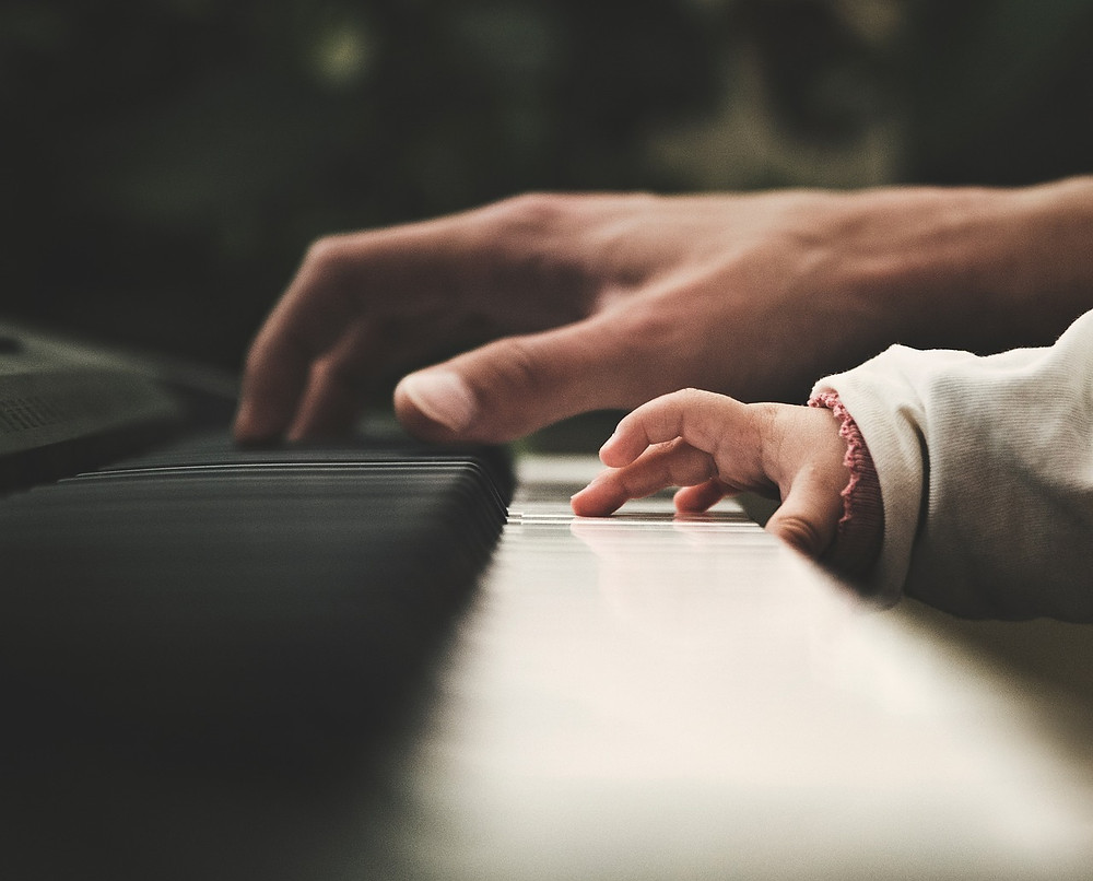 Adult and child playing piano