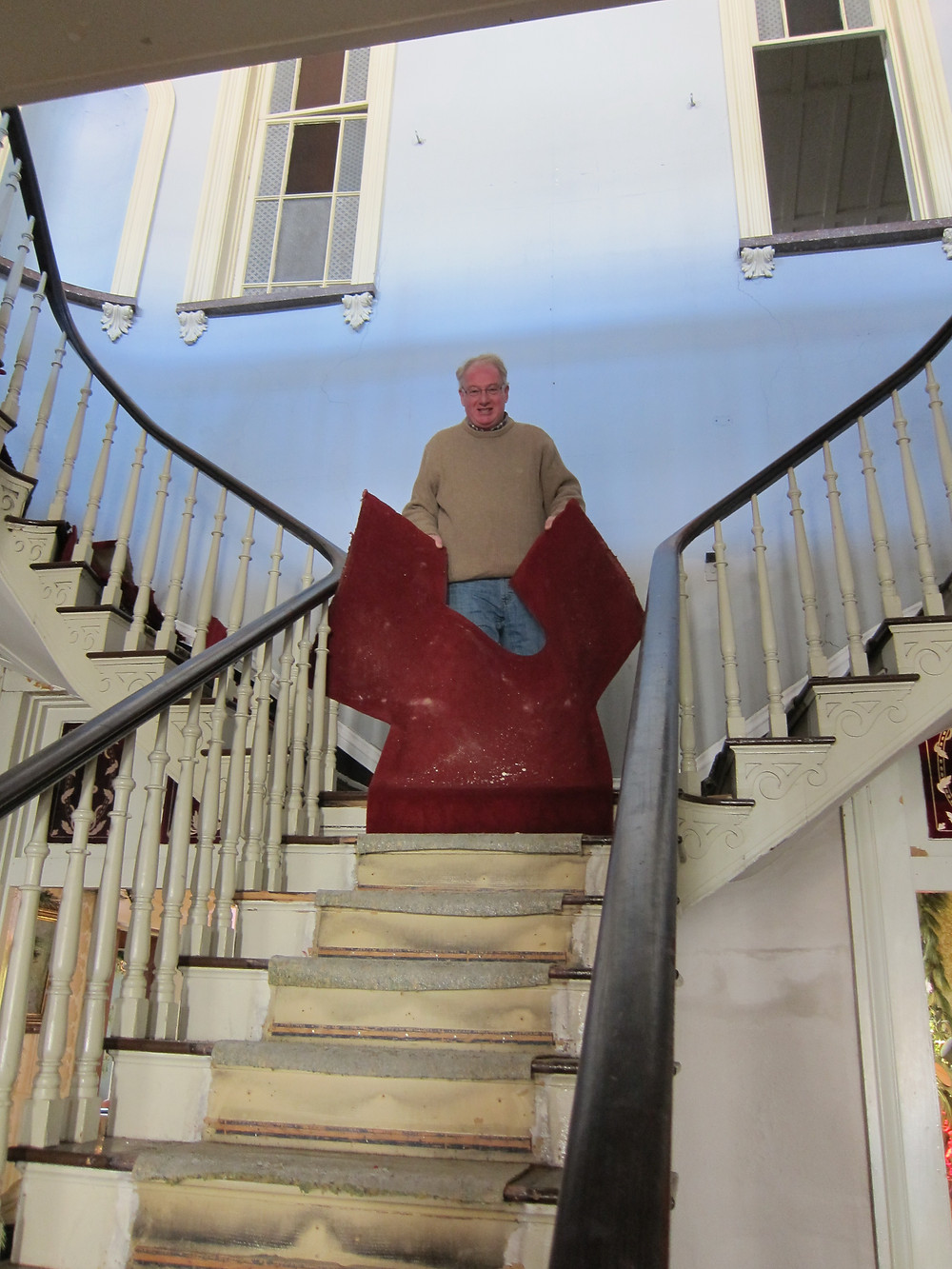Curator Jerry Trescott removes the last of 1990s carpet from the staircase.