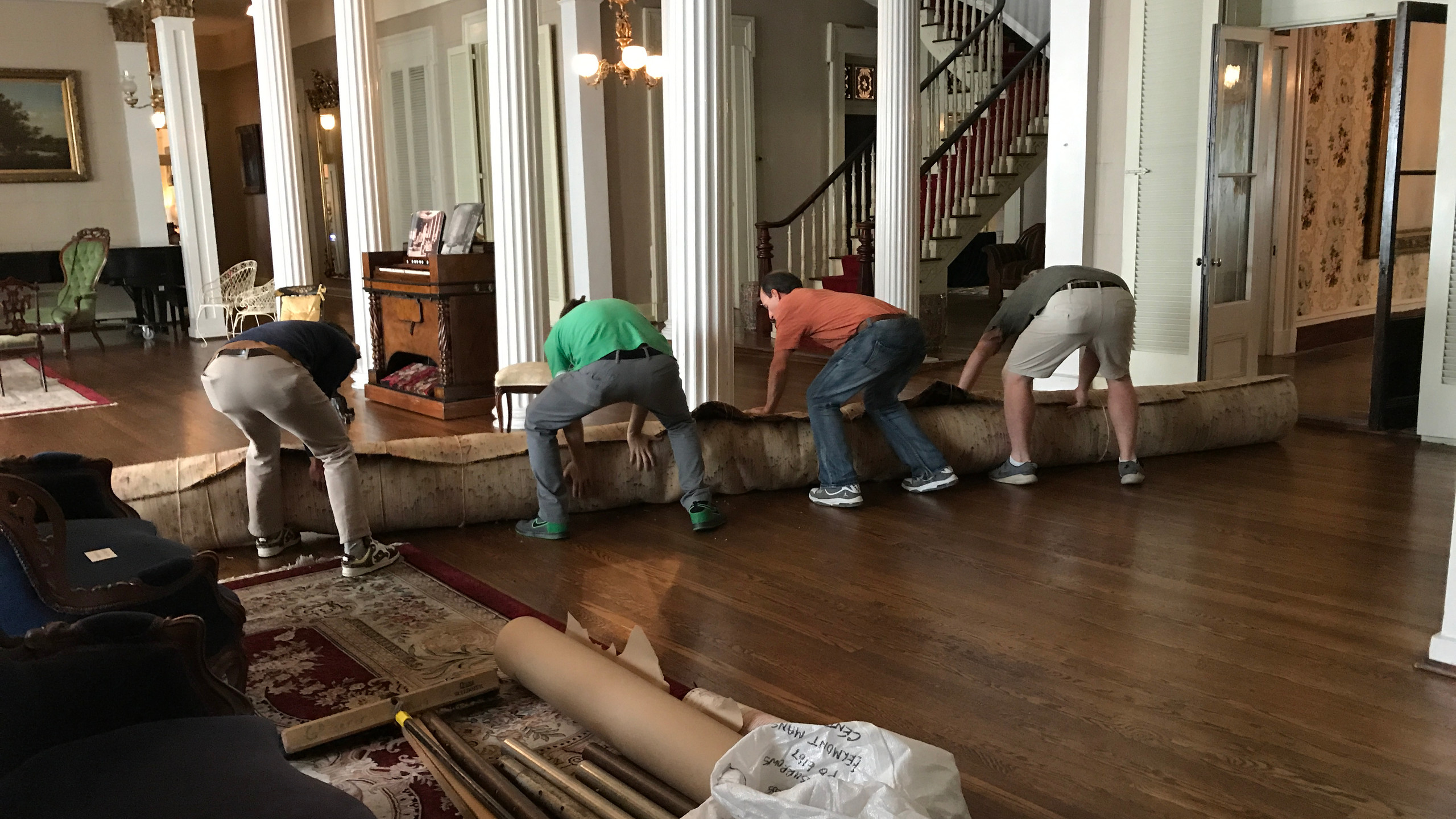 The installation crew works to move the carpet into the Central Parlor