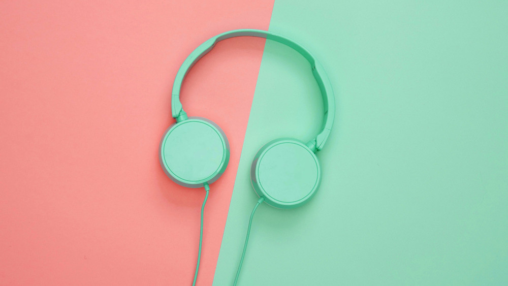 Mint green headphones on a background of half coral and mint green.