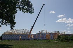 Standing trusses with a crane on this old limestone house and addition.