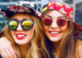 Close up fashion portrait of two sisters hugs and having fun together, wearing bright floral hats an