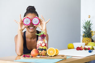 Woman smiling with a tropical fruit salad, being playful covering her eyes with dragon fruit_edited_
