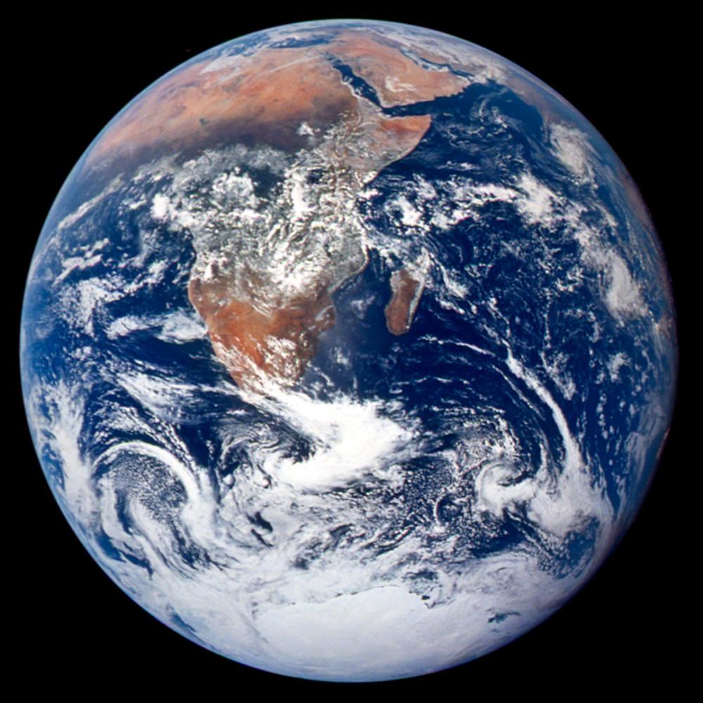 Foto da Terra vista do espaço com os continentes africano ao centro e a antártico embaixo rodeados pelo oceano azul coberto de nuvens.