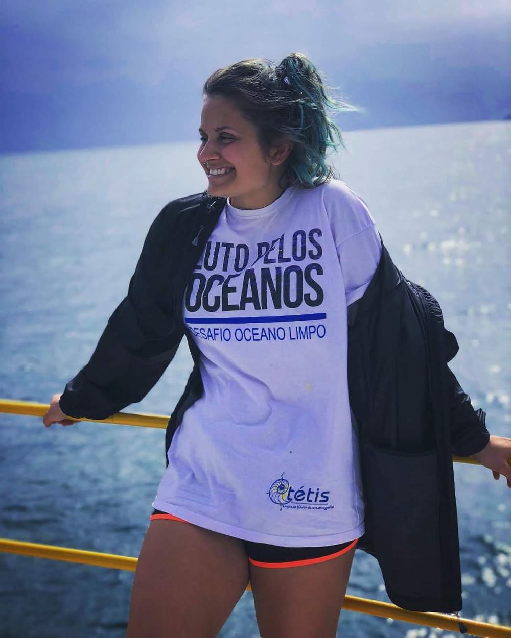 Imagem de Natasha Costa encostada em um corrimão com o mar ao fundo. Ela está com os cabelos presos, sorrindo e olhando para seu lado direito, vestindo uma blusa que tem a frase Luto pelos oceanos/ Desafio oceano limpo, com um casaco preto e um short curto