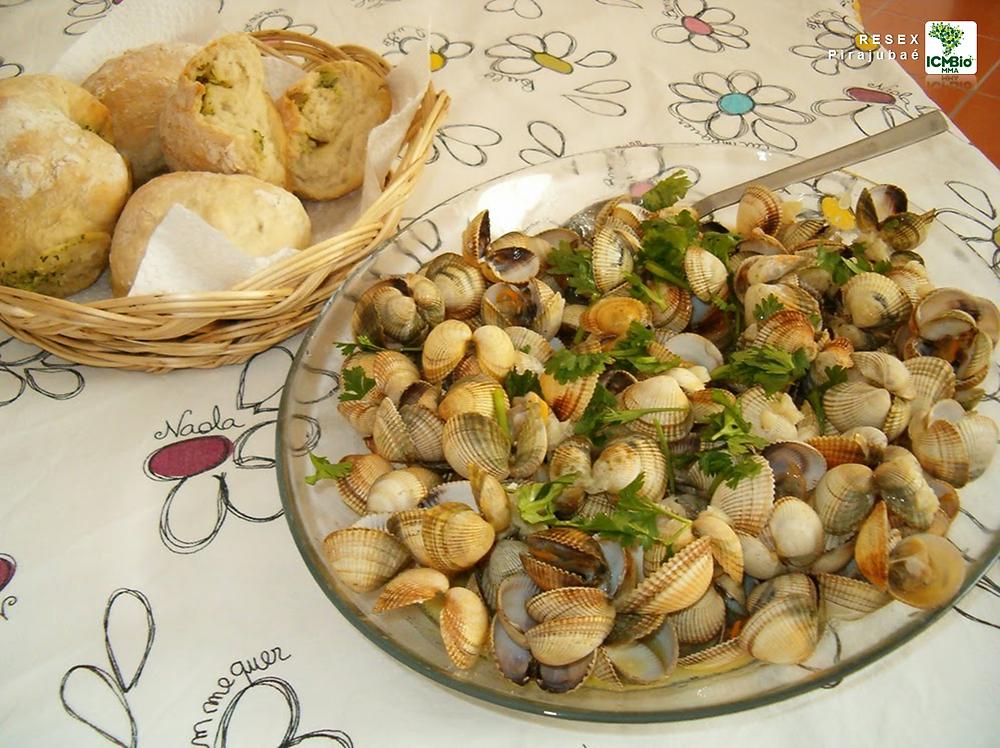 Prato de berbigão ao bafo, servido com pãezinhos, sobre uma toalha de mesa com várias flores desenhadas com lápis, sem preenchimento