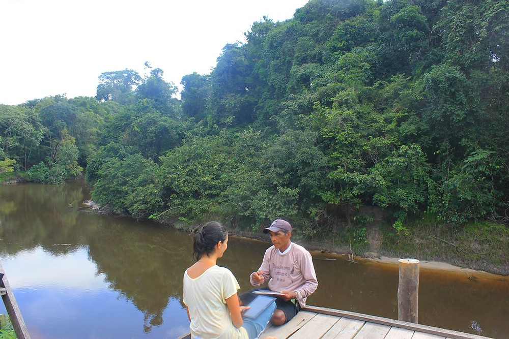 Franciany entrevistando um morador de terras indígenas, sentados a beira de um rio com uma floresta de mata fechada ao fundo