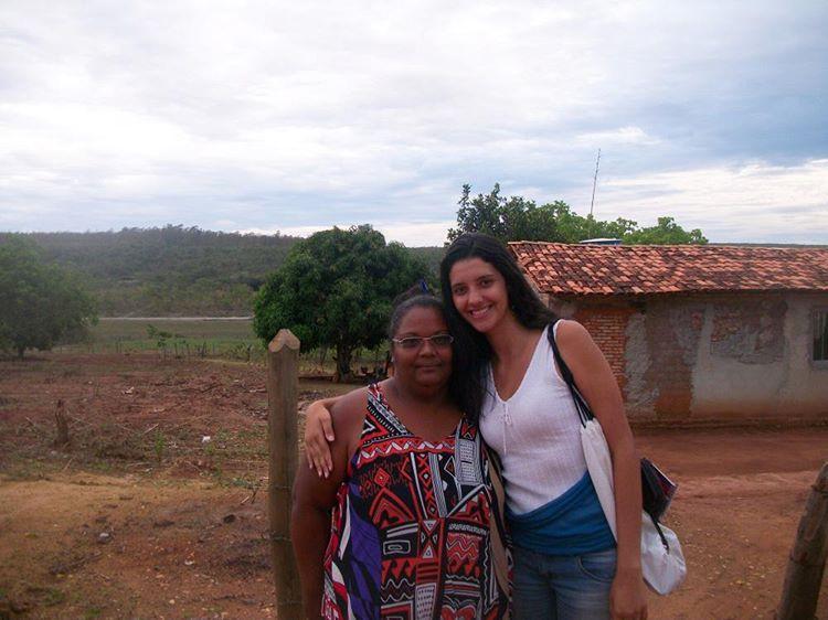 Na foto a pesquisadora Franciany está abraçada com a entrevistada, moradora da região do Norte de Minas. Elas estão em um ambiente de zona rural, com uma casa simples ao fundo.