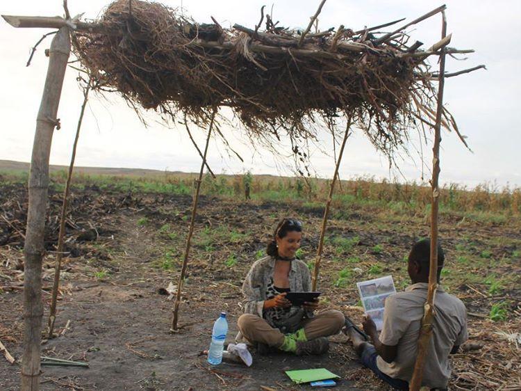 Franciany entrevistando um caçador angolando debaixo de uma estrutura para dar sombra, feita de madeira e palha.